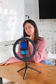 스마트 폰에 비디오를 녹화하고 링 램프로 자신을 조명하는 소녀