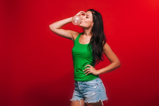 Girl on a red background blowing bubbles of gum