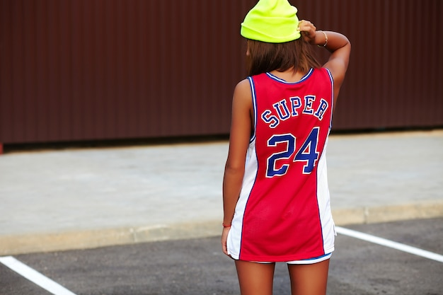 Girl in red basketball sports clothes sitting on asphalt