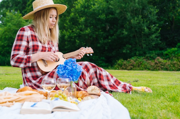 Girl in red checkered dress and hat sitting on white knit picnic blanket plays ukulele and drinking wine.
