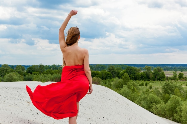 A girl in a red cloth on the sand poses for a photographer against the backdrop of a cloudy sky. red fabric in the wind hugs the girl's figure.