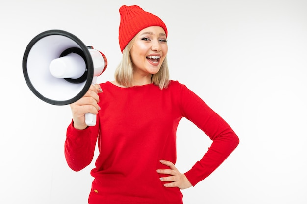 Girl in red clothes with a megaphone in hands shouts on a white