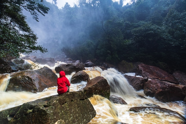 A girl in a red coat sitting  on the rock in the rainforest stream.