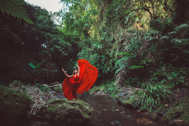 Girl in a red dress dancing in a waterfall.