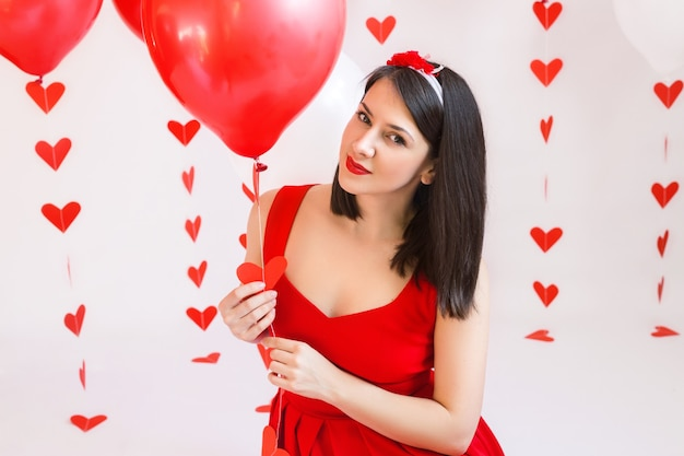 A girl in a red dress holds a balloon with a garland of hearts.