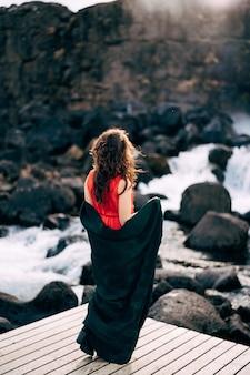 A girl in a red dress near ehsaraurfoss falls, ehsarau river, national park, tingwedlir, sudurland