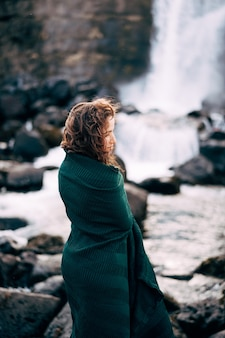 A girl in a red dress near ehsaraurfoss falls ehsarau river national park tingwedlir sudurland