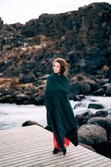 A girl in a red dress near ehsaraurfoss falls ehsarau
