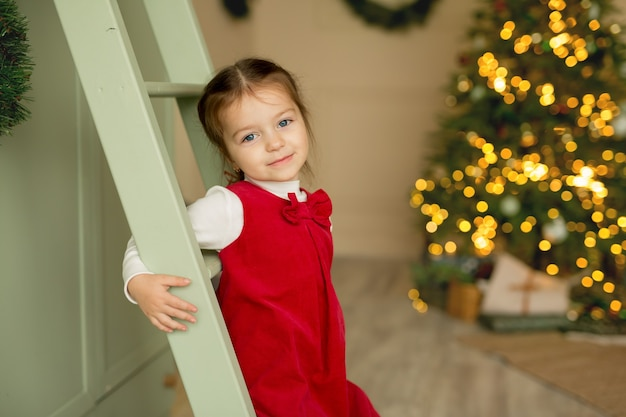 A girl in a red dress stands in a room with a christmas tree and smiles sweetly