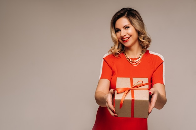 A girl in a red dress stands with gifts in her hands on a gray background