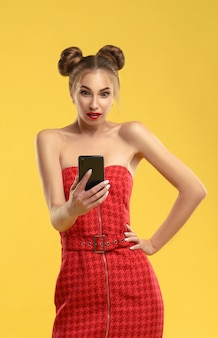 Girl in red dress with hair buns surprised and looking to smartphone on yellow wall