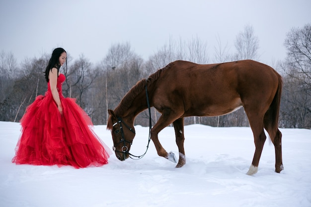 Girl in a red dress, with a horse, winter, brunette