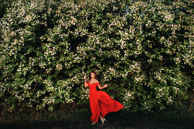 A girl in a red dress with red lips stands next to a large white flowering tree at sunset.