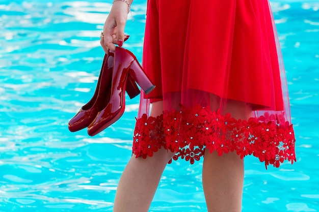 Girl in a red dress and with red shoes in hand at the pool_