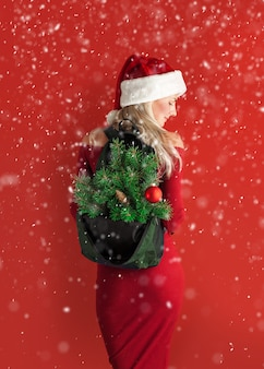Girl in a red dress with santa hat with a backpack out of which the branches of a new year tree stick out