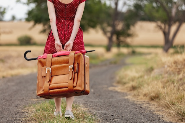 Girl in red dress with a suitcase on a rural road before the rain