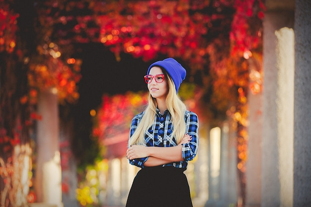 Girl in red glasses and shirt in a red grapes alley.