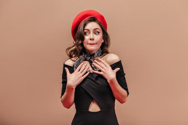 La ragazza in cappello rosso e vestito nero si sente a disagio. colpo di giovane donna su sfondo beige.