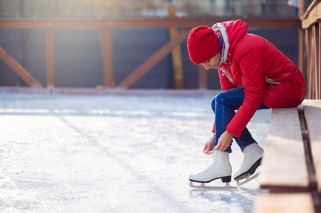 Girl in a red jacket sits on a bench on an open ice rink and laces figure skates