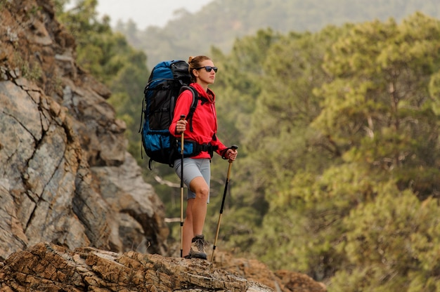 Girl in red jacket standing on the rock with hiking backpack