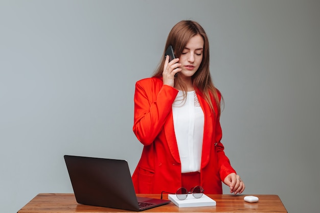 Girl in a red jacket talking on the phone while using laptop