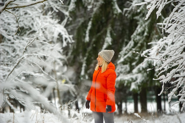 A girl in a red jacket walks through a snowy forest in winter