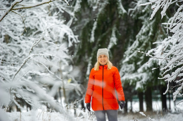 A girl in a red jacket walks through a snowy forest in winter.