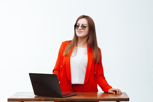 Girl in a red jacket working at the computer on a white background