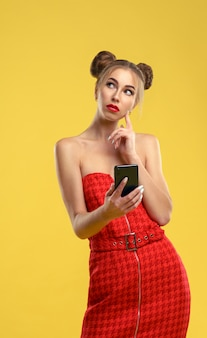 Girl in red off shoulder dress holding a smartphone looking up and thinking on yellow wall