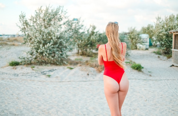 Girl in a red one-piece swimsuit on the sandy beach of the sea coast at sunset