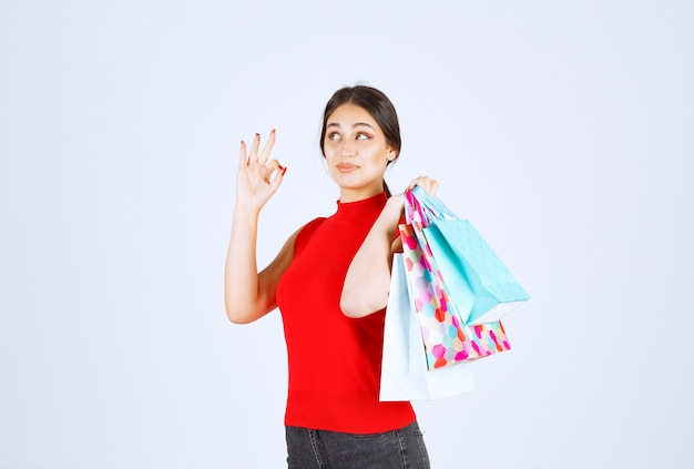 Girl in red shirt carrying colorful shopping bags behind her shoulder.