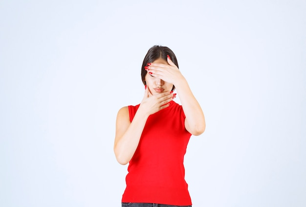 Girl in red shirt covering part of her face with hand.