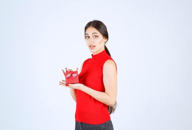 Ragazza in camicia rossa che dimostra la sua confezione regalo rossa.