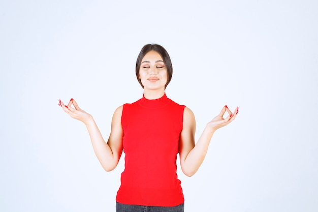 Ragazza in camicia rossa che fa meditazione.