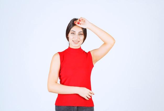 Ragazza in camicia rossa che dà pose adorabili e seducenti.