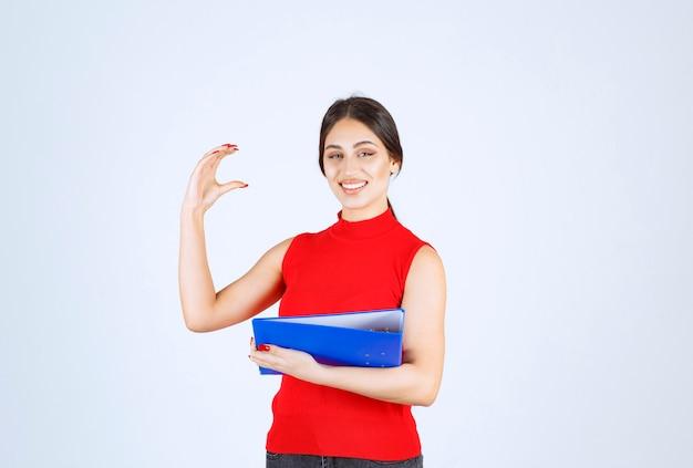 Ragazza in camicia rossa che tiene una cartella aziendale blu.