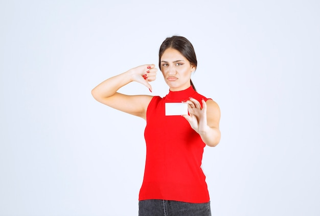 Girl in red shirt holding a business card and looks confused and dissatisfied.