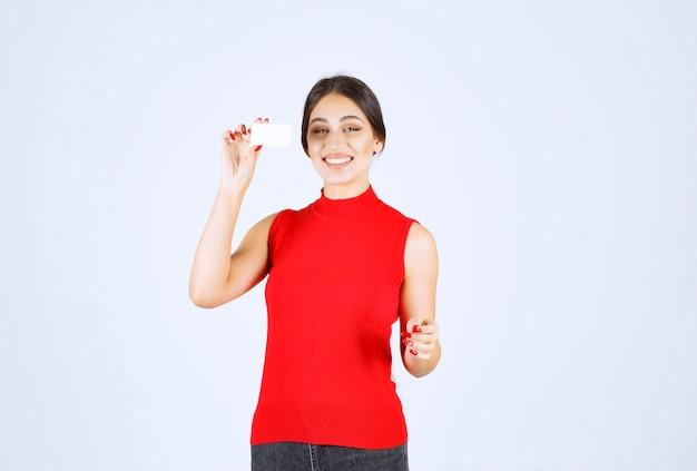 Ragazza in camicia rossa che tiene un biglietto da visita e sembra soddisfatta.