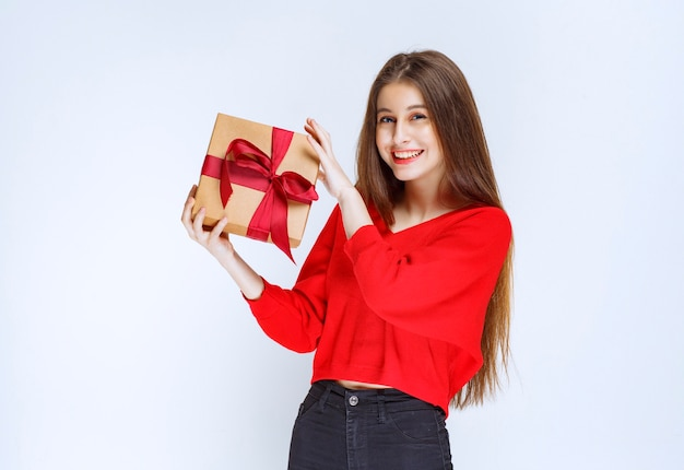 Girl in red shirt holding a cardboard gift box wrapped with red ribbon.