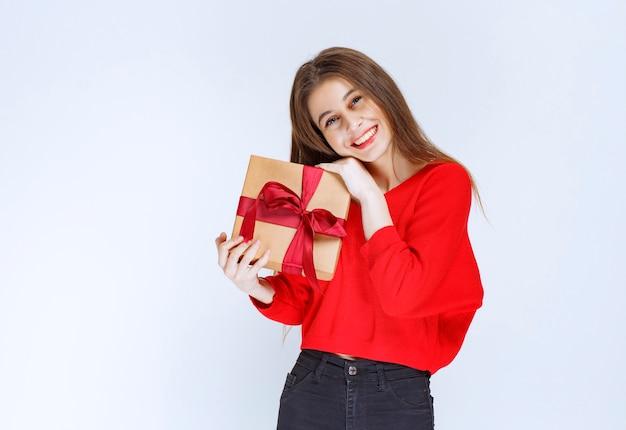 Ragazza in camicia rossa che tiene una scatola regalo di cartone avvolta con nastro rosso.