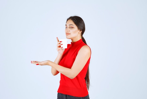 Girl in red shirt holding a coffee cup and smelling.