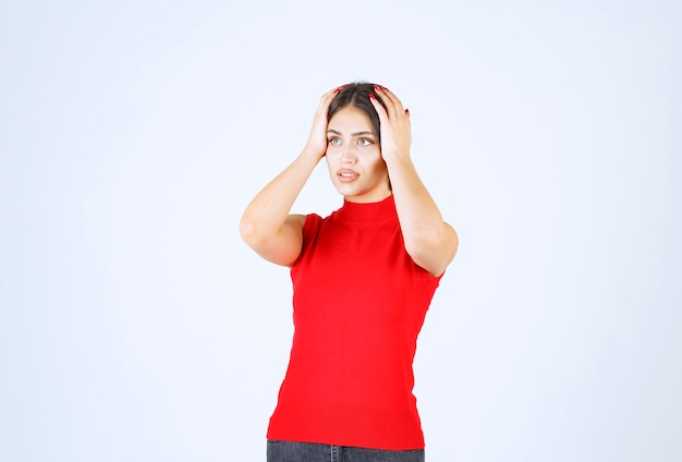 Girl in red shirt holding her head with hands as she has headache.