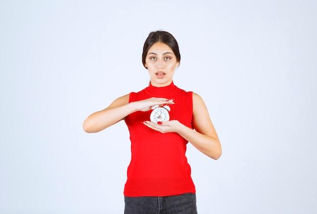Ragazza in camicia rossa che tiene e promuove una sveglia.