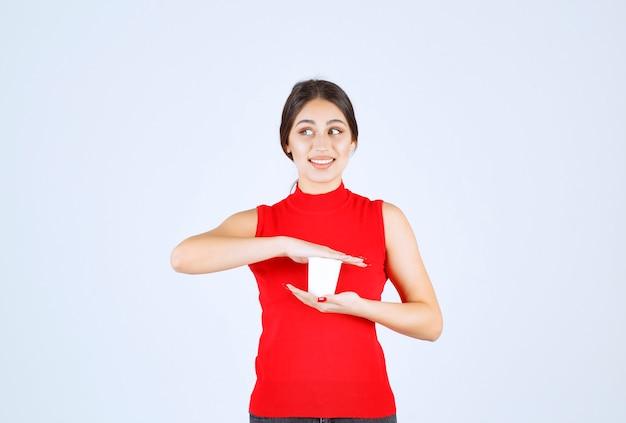 Ragazza in una camicia rossa che tiene una tazza di caffè bianco tra le mani.