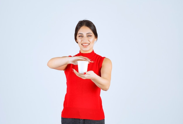 Girl in a red shirt holding a white coffee cup between hands.