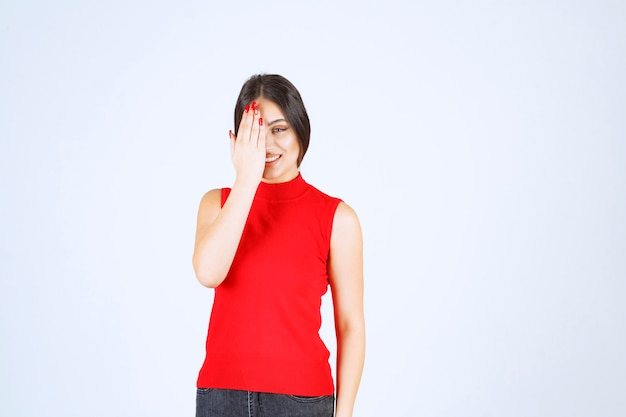 Girl in red shirt looking through her fingers.