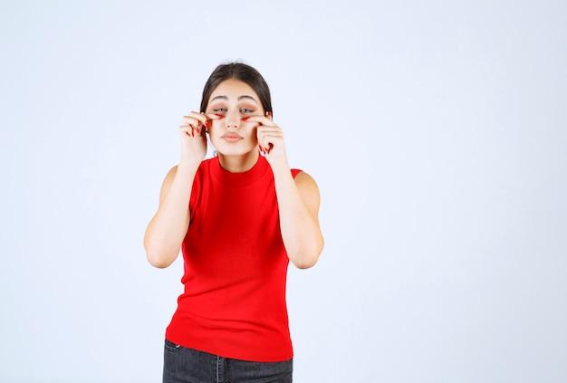 Ragazza in camicia rossa che guarda tra le dita.