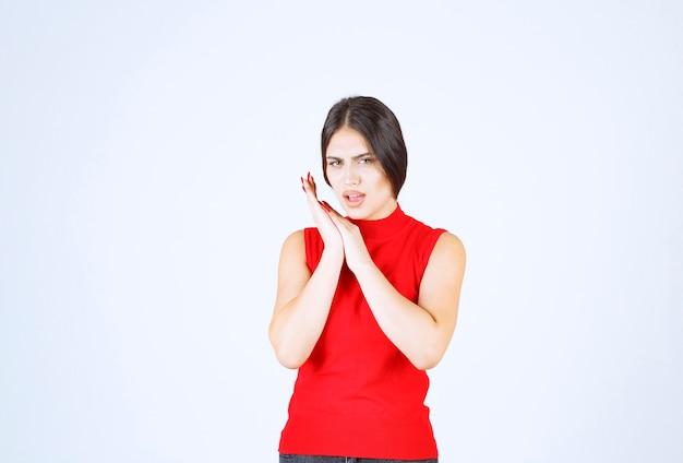 La ragazza in camicia rossa sembra triste e delusa.