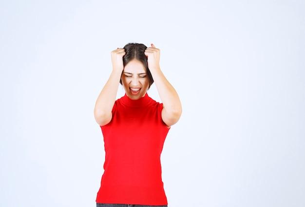 La ragazza in camicia rossa sembra stressata e nervosa.
