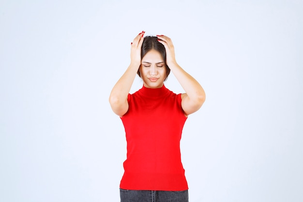 Girl in red shirt looks stressed and nervous.